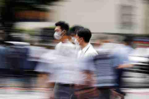 Men wearing masks cross a street in Seoul, South Korea.