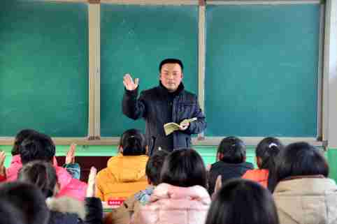 """--FILE--A male Chinese teacher gives a lesson to his students in a classroom at a junior high school in Shiziyuan town, Shenxian county, Liaocheng city, east China's Shandong province, 13 January 2015.Worried that a shortage of male teachers has produced a generation of timid, self-centred and effeminate boys, educators in China are working to reinforce traditional gender roles and values in the classroom. In Zhengzhou, a city on the southern bank of the Yellow River, schools have asked boys to sign petitions pledging to act like """"real men"""". In Shanghai, principals are trying boys-only classes, with courses like martial arts, computer repair and physics. In Hangzhou, in eastern China, educators have started a summer camp called """"West Point Boys"""", complete with taekwon-do classes and the motto: """"We bring out the men in boys."""" Education officials across China are aggressively recruiting male teachers, as the domestic news media warns of a need to """"salvage masculinity in schools"""".No Use China. No Use France."""