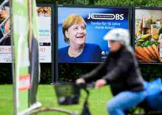 """An advertisement showing German Chancellor Angela Merkel with a slogan reading: """"Thanks For 16 Years of Hard Work"""" is seen behind election posters for Germany's upcoming state elections in Brunswick, Germany, September 16, 2021. REUTERS/Fabian Bimmer"""