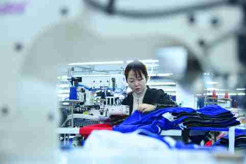 Workers make clothes at an apparel manufacturing company in Enshi city, south China's Hubei province, 21 November 2020.Xuan'en County introduced apparel manufacturing enterprises beside the relocation sites in Shadaogou Town and Gaoluo Town to help with employment. So far, it has helped more than 900 people who were relocated to obtain employment and increase income.No Use China. No Use France.