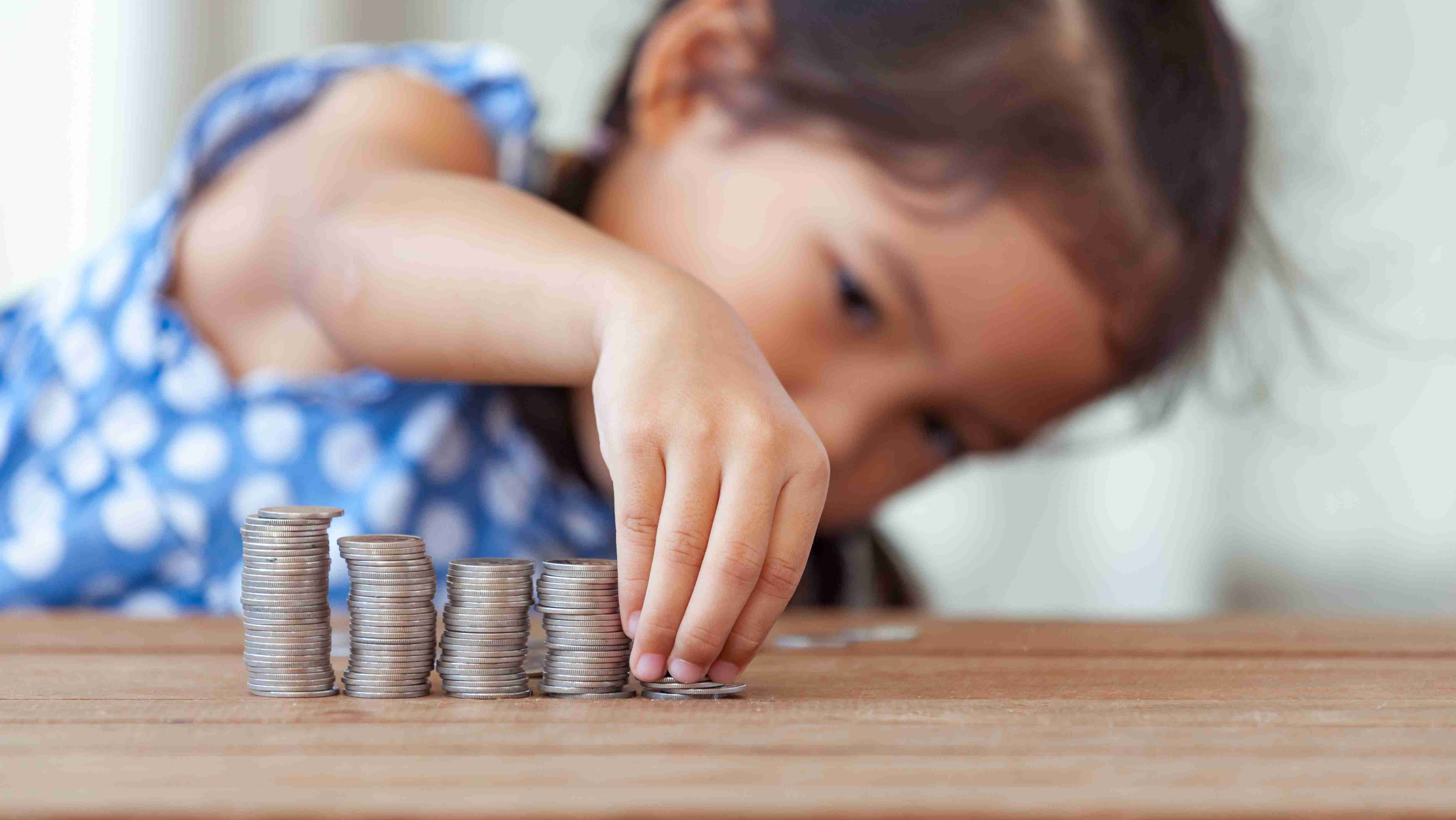 Young girl lining up stacks of coins