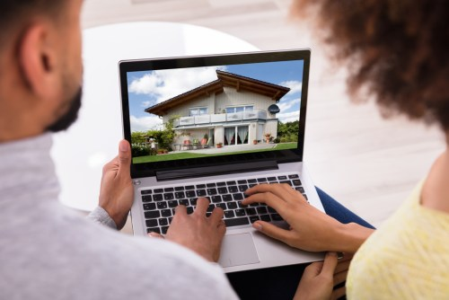 Couple looking at houses on laptop