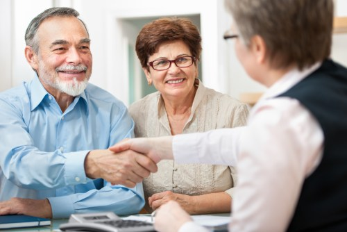 Happy Couple shaking hands with trusted real estate agent