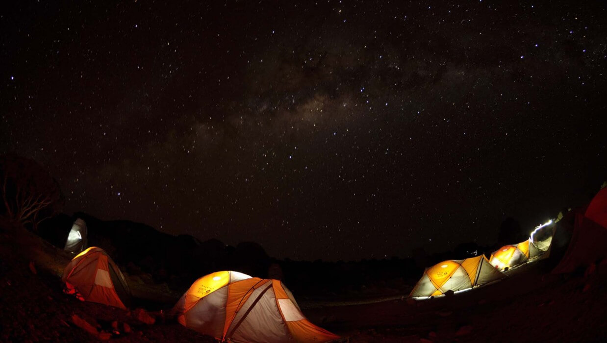 group of tents with lights on at night under the stars and milky way galaxy