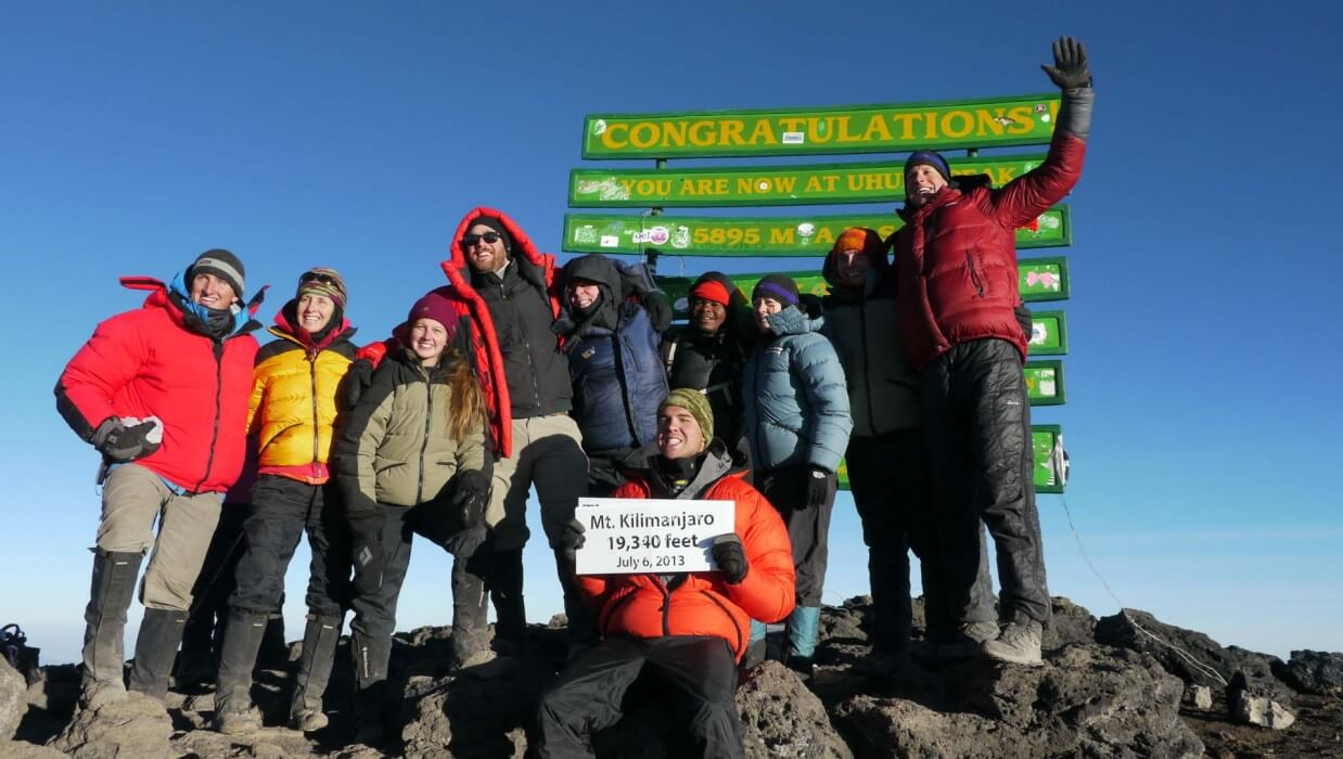 group of climbers that have reached the summit of Mt Kilimanjaro holding a sign saying 19340 ft July 6 2013