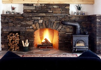 Weathered Fieldstone Fireplace, Arched Opening, Woodbox, Flush Flagstone Hearth, Woodstove