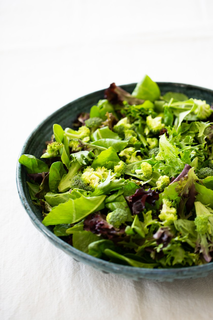 greens and raw broccoli, an apple and pommegrante.