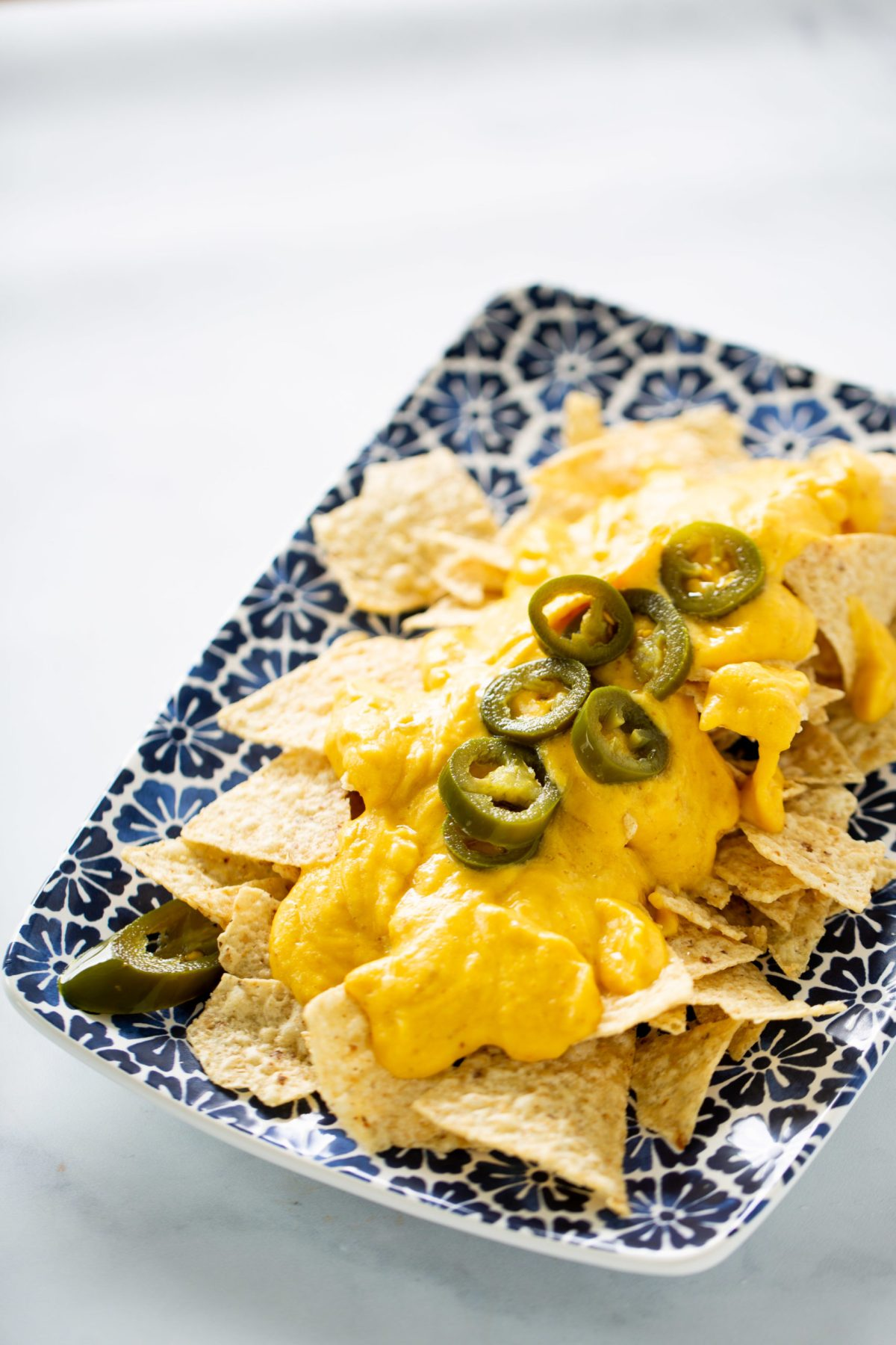 VEgan Queso with nachos and jalapeño slices