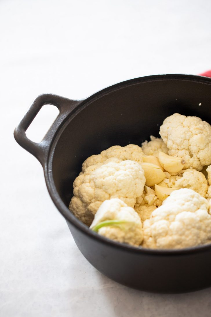 cauliflower florets in a pot with garlic cloves