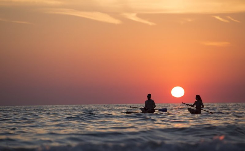 Two kayakers resting in calm water in front of a bright orange sunset. Peaceful.