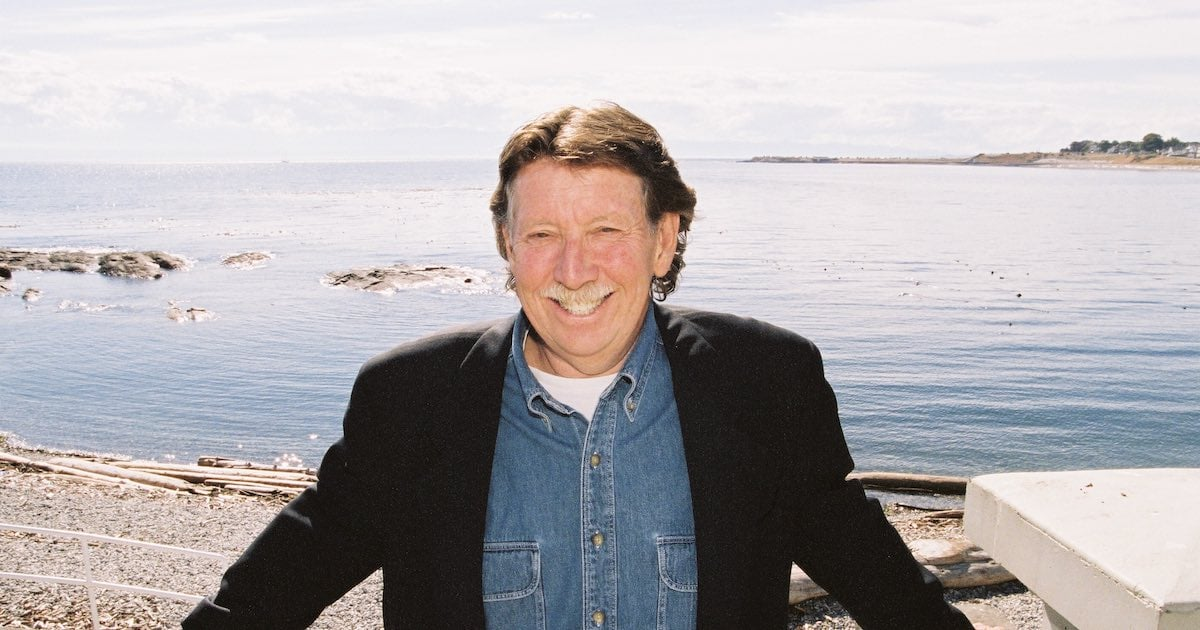 Bruce Elkin grinning on the beach at Ross Bay, Victoria, BC