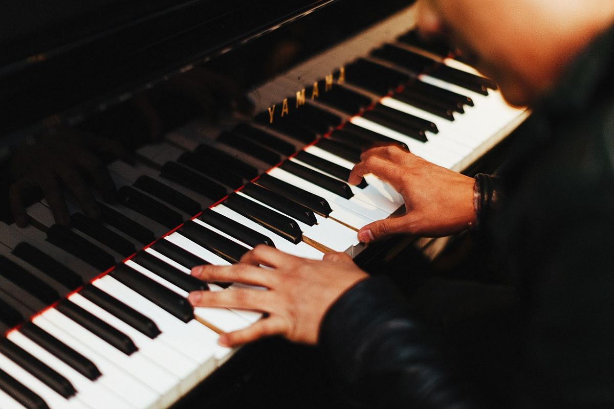 Close up of of person practicing piano, just fingers on keys