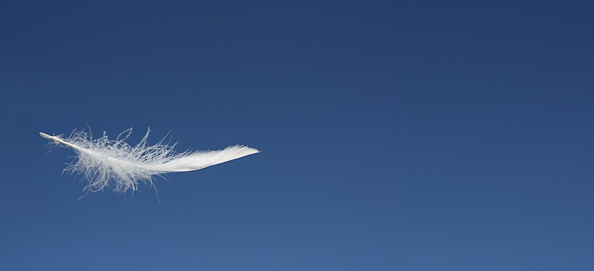 White feather floating in the air, with a deep blue sky behind it.