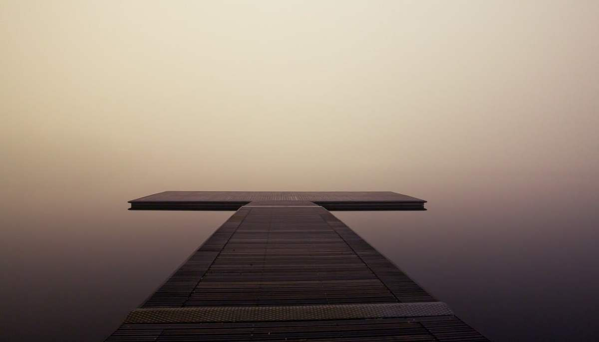A simple wooden dock extending into lake cloaked in cloud