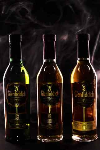 3 bottles of Glenfiddich Scotch silouetted against against a black background.