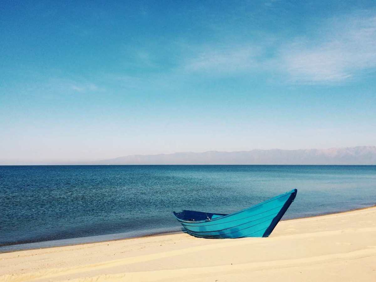 A dark blue wooden boat sits on a sandy beach above deeper blue water. In the background a hazy mix of blue sky and wispy clouds sits above a blurred ridge or island