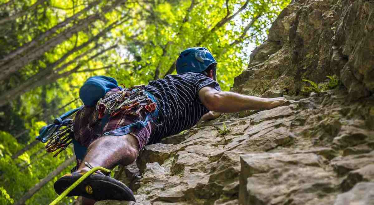 An executive at a team building retreat is spread out on steep rock slope, looking for his next hold and step. He's wearing a blue helmet, a blue and white stripped t-shirt and rock climbing shoes. Behind him and to the left side, sun lights up a forest of beech or birch.