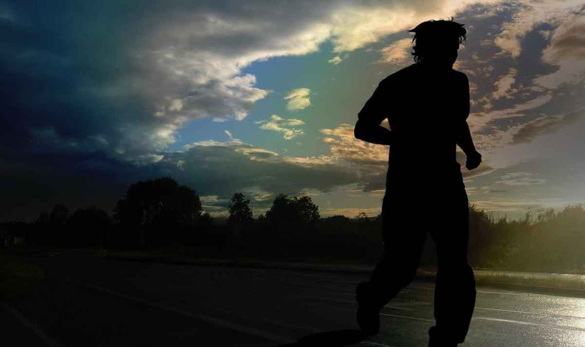 Runner with wet, messy hair, silhouetted agains a stormy cloud. Evening coming on.