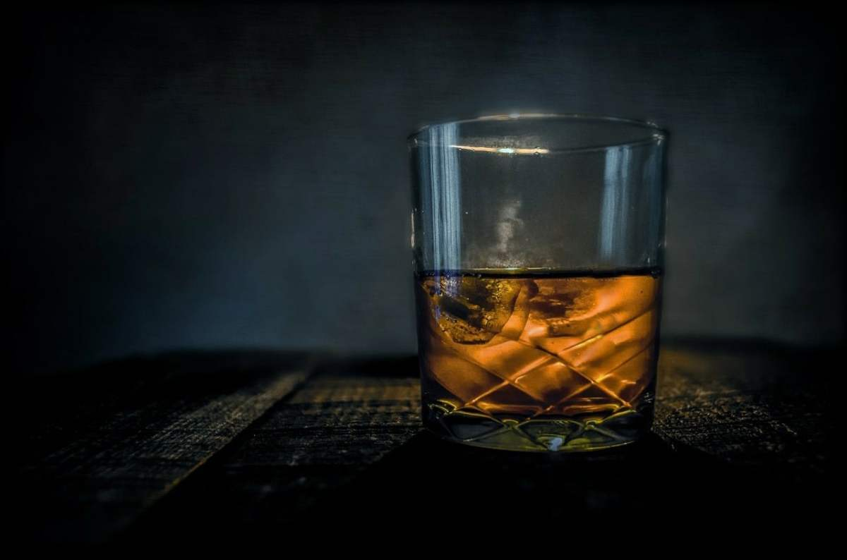 A back-lit, half glass of Scotch Whisky sits on a patterned table top. The back ground is grey toned shading.