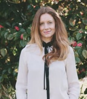 Writer, Sarah Pollard, stands in front of a wall of ivy. She has long blondish red hair and wears a long, ivory shirt with a narrow black tie. She's smiling.