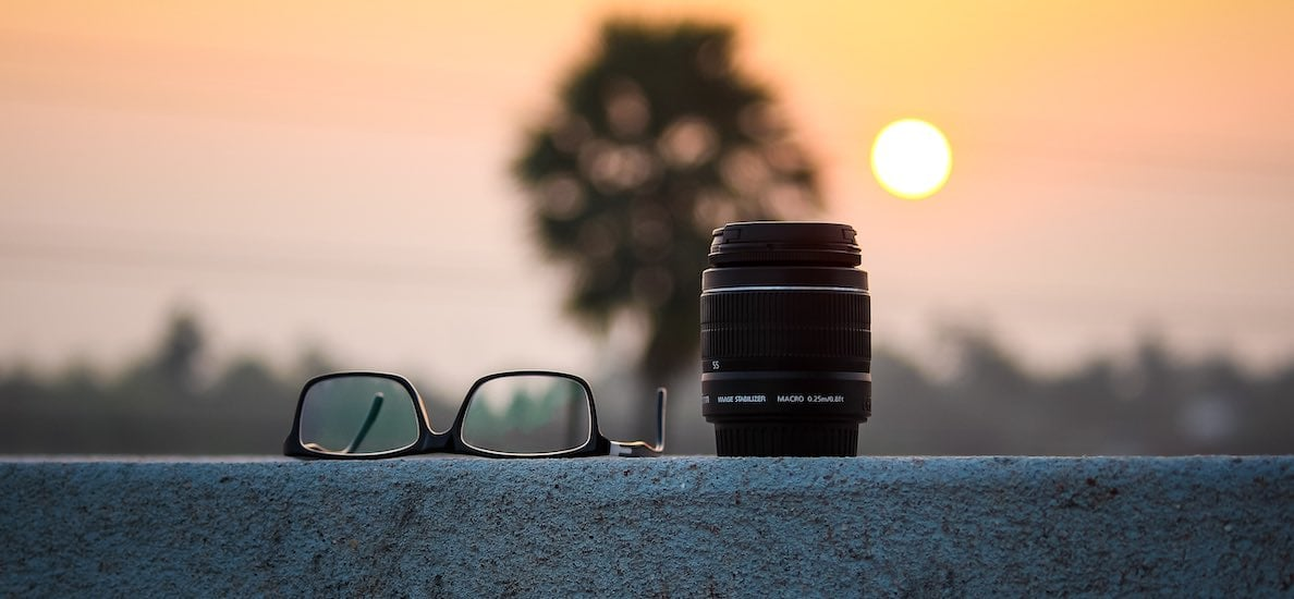 A pair of glasses and a camera lens sit on a concrete wall. In the background, a low sun lights up a blurry tree