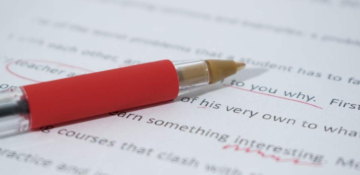 A red ballpoint pen sits atop a page of writing that has editing marks on it