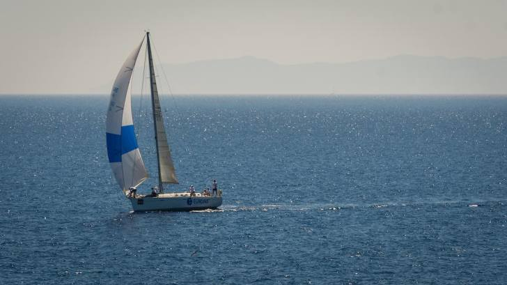 A white sailboat with a blue and white sail plies open blue water. In the background, a hazy sky obscures a mountain range.