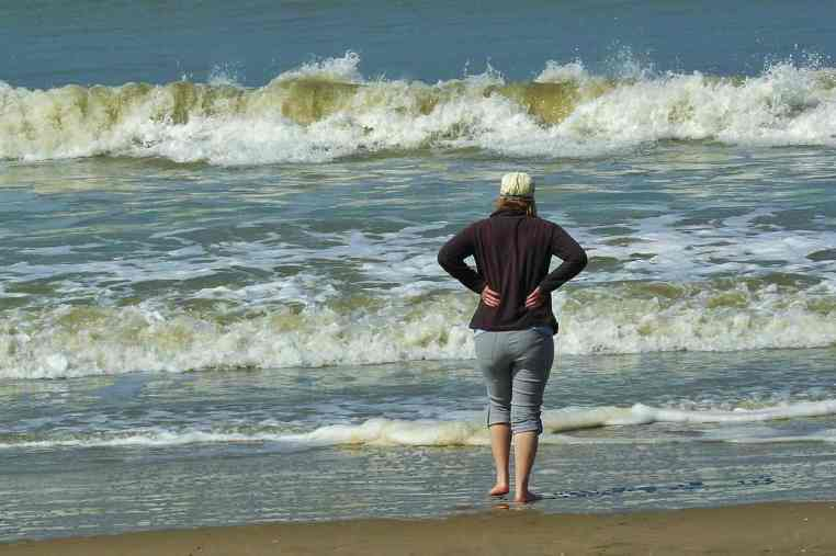 Woman standing beachside, watching the surf roll in, and breathing fresh air.