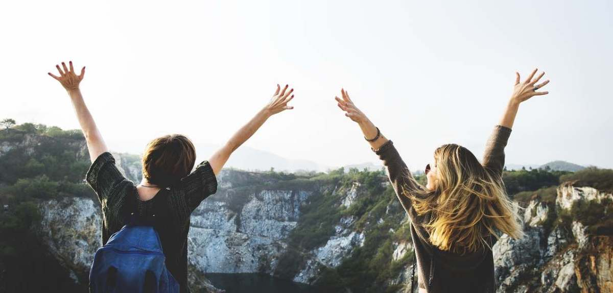 Two participants in a women's outdoor program with arms upraised looking out over a rocky canyon.