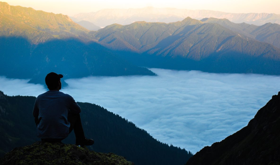 A man sits on a hillside looking across a cloud filled valley at mountain ranges partly lit by a rising sun—contemplating simplicity and success
