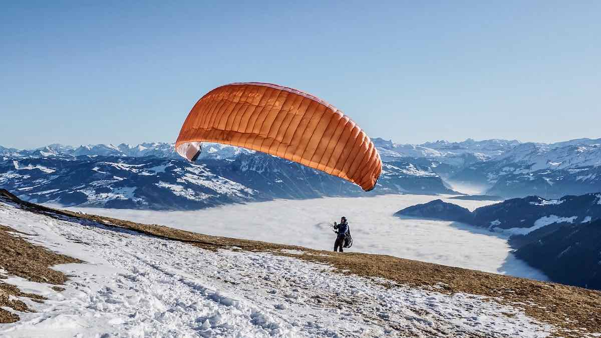 The simple yet complex structure of paraglider on a ridge above a mountain valley