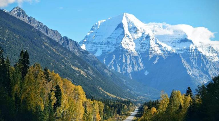 Resilient mountain range above steep forested slopes and a winding road. Blue sky background