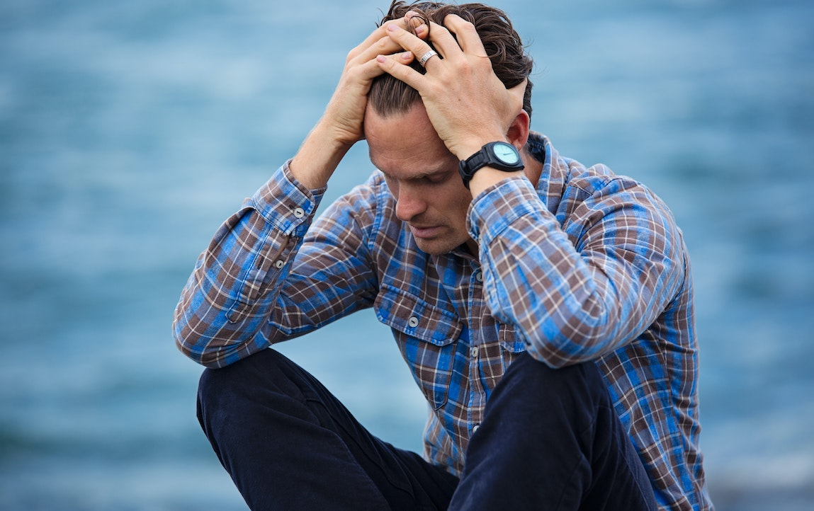 A frustrated man sits with his elbows on is knees, has hand on the sides of his head. He's wearing a green and blue checkered shirt, blue jeans an a fancy black watch. Background is partly clouded sky