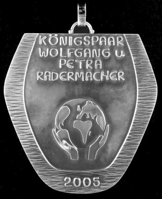 Die Königsplakette von Wolfgang und Petra Radermacher zeigt die Weltkugel, getragen in goldenen Händen. Dieses Motiv wurde ausgewählt, da Wolfgang in zahlreichen Ländern der Erde tätig ist.