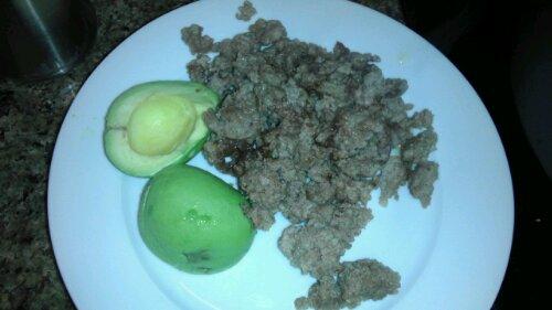 Pork and pork pan sausage with avocado on a white plate