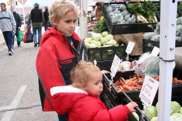 Kids look at vegetable bins
