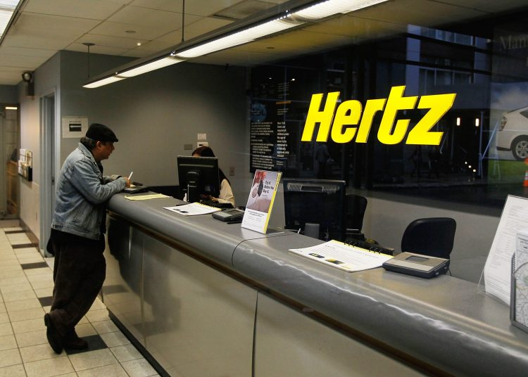 NEW YORK - APRIL 26:  A man stands at the counter of a Hertz car rental location April 26, 2010 in New York City.  Hertz Global Holdings Inc. has announced that it will buy Dollar Thrifty Automotive Group for over one billion dollars in cash and stock.  (Photo by Chris Hondros/Getty Images)