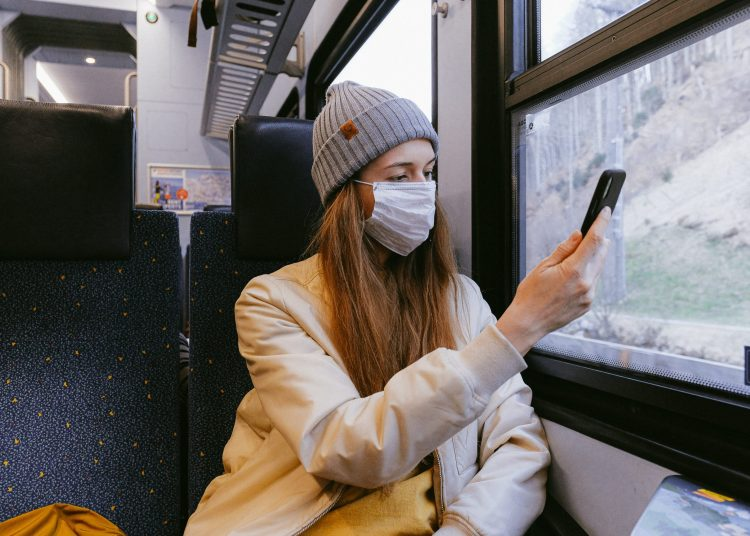 woman in beige jacket and gray knit cap holding smartphone 3962218 scaled
