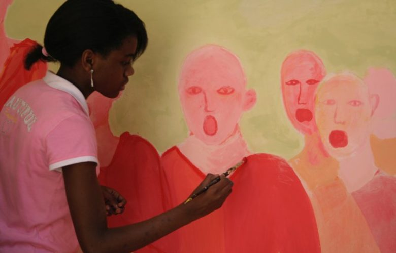 alunna che dipinge su una parete