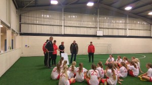 Jamie Carragher and members of the Jamie Carragher Sports & Learning Academy delivering a coaching session to girls football team visiting from Norway.