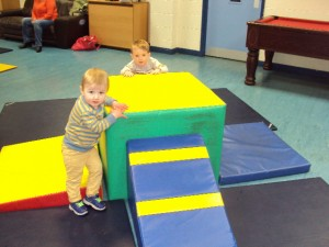 Toddlers group using soft play equipment.
