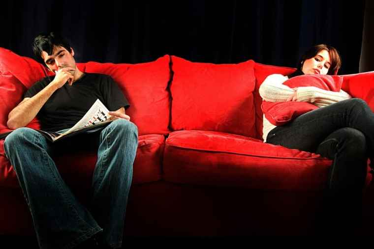 couple sitting passively on opposite ends of couch