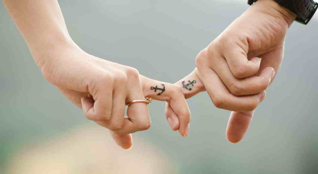 couple locking fingers with anchor tatoos; how to have a healthy marriage