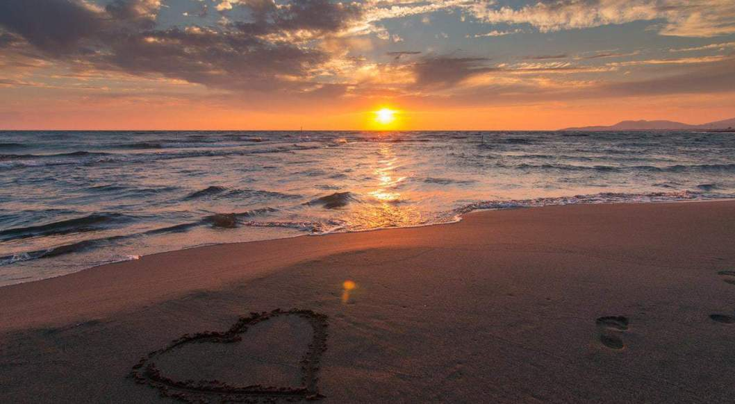 on Christian marriage heart on sand with sunset in background