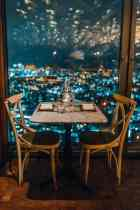 table and chairs with romantic view of the city at night