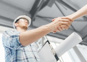 San Antonio Contracts Lawyer builder with blueprint shaking partner hand