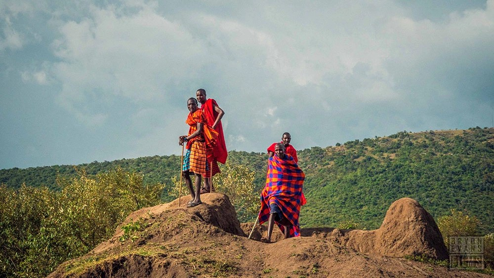 Four Kenyan people standing on a cliff.