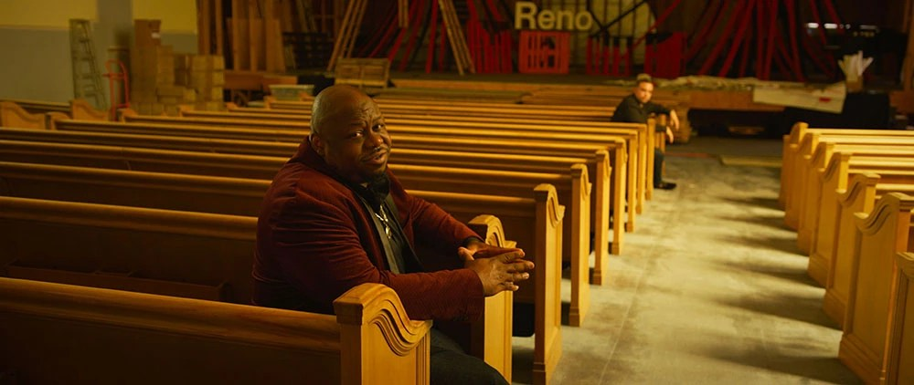 frame grab of two men sitting on theater benches