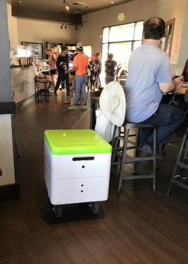 "A Robby Technologies prototype delivery robot navigates through a Starbucks in Palo Alto on Monday, Aug. 28, 2017. If it senses someone in front of it, its gentle female voice says, ""Excuse me."" (John Orr / Daily News)"