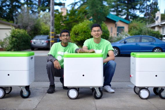 Dheera Venkatraman, left, and Rui Li, co-founders of Robby Technologies, with a few of their prototype delivery robots in an undated photograph. (Dheera Venkatraman / Robby Technologies)